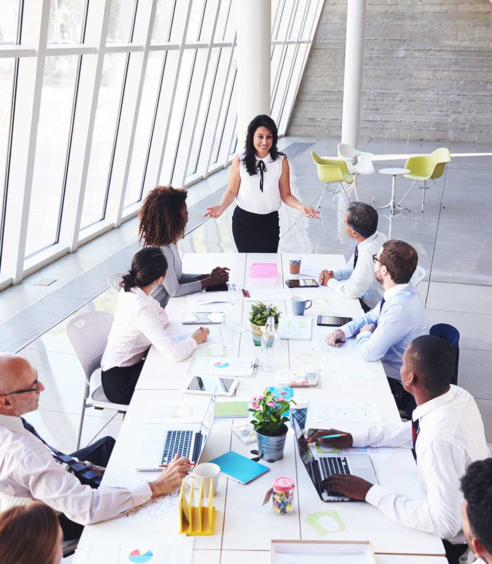 Employee presenting to fellow staff members who are sitting around a table